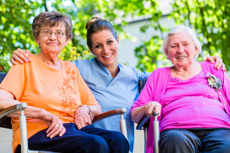 Geriatric nurse having chat with senior women royalty free stock image