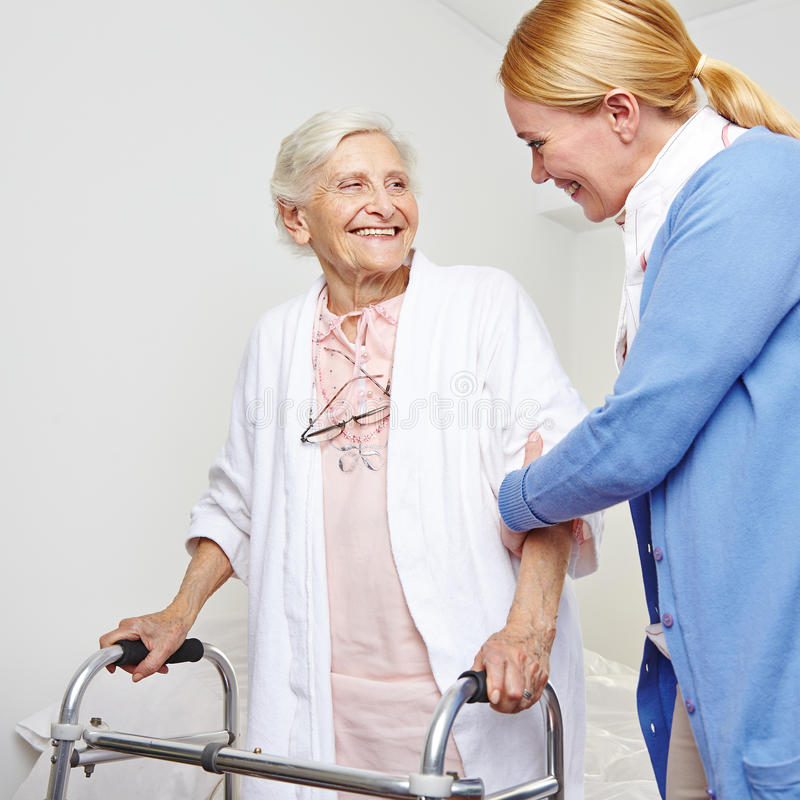 Geriatric nurse helping senior. Citizen women with walker royalty free stock images