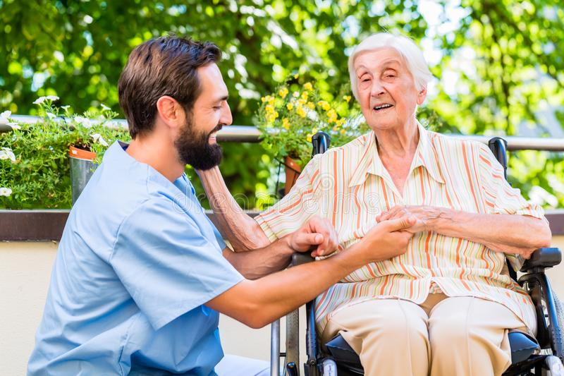 Geriatric nurse holding hand of old woman in rest home. Geriatric nurse holding hand of happy old women in rest home royalty free stock photos