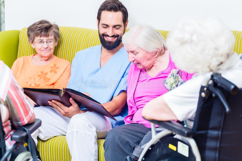 Geriatric nurse looking at pictures with seniors. In nursery home royalty free stock photography