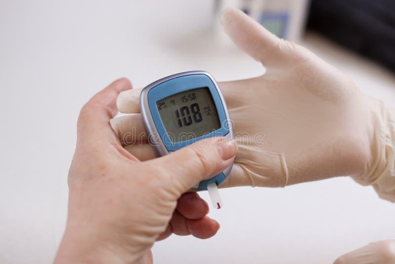 Geriatric nurse measures the glucose level royalty free stock photos