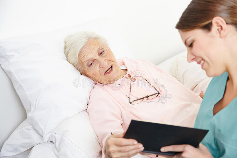 Geriatric nurse reading book. To senior citizen women in bed royalty free stock images