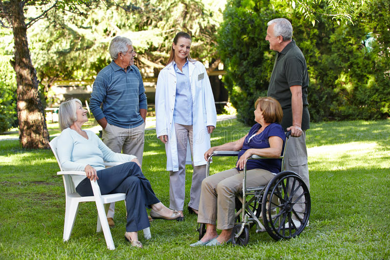 Geriatric nurse with senior group. In garden of a retirement home royalty free stock photos