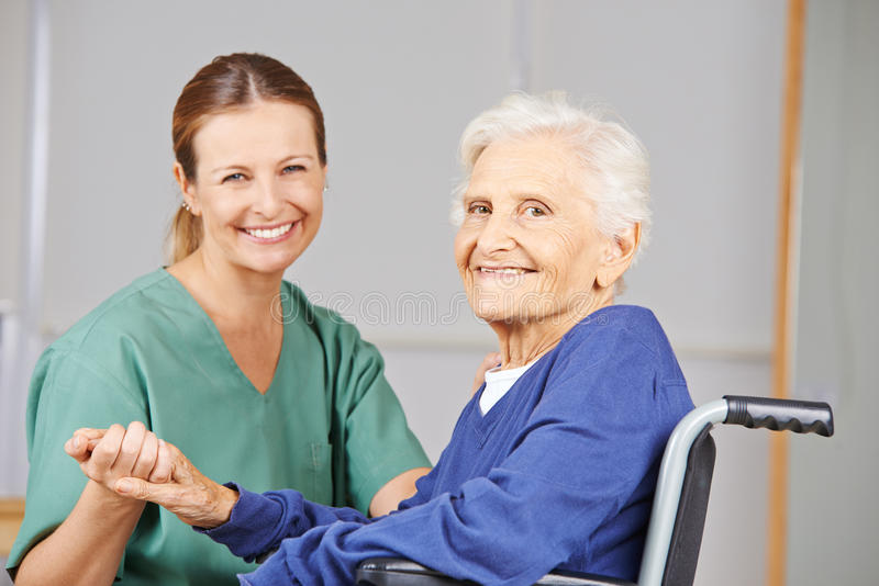 Geriatric nurse and senior woman in wheelchair. Geriatric nurse and senior women in wheelchair smiling together in nursing home stock image