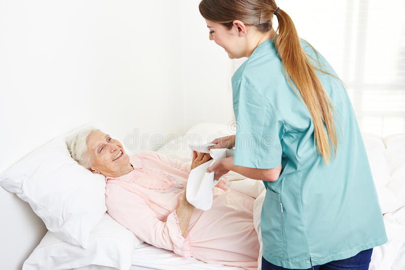 Geriatric nurse washing bedridden. Senior women and drying her hands in nursing home royalty free stock images