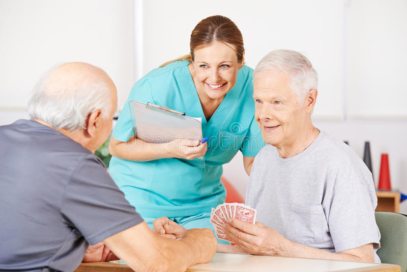 Geriatric nurse watching old men playying cards. Smiling geriatric nurse watching twi old men playying cards in a nursing home stock image