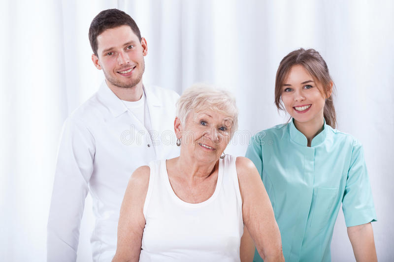 Geriatric patient with her physiotherapists. Happy geriatric patient with her young physiotherapists stock photo