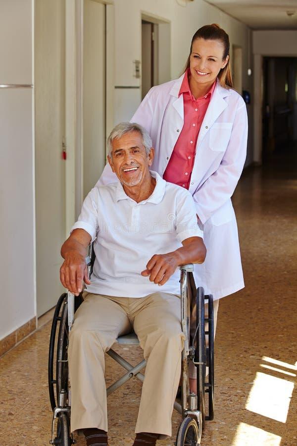 Geriatric sjuksköterska med den höga manen i rullstol arkivbild