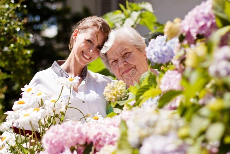 Geriatrische verpleegster met bejaarde in de tuin royalty-vrije stock foto