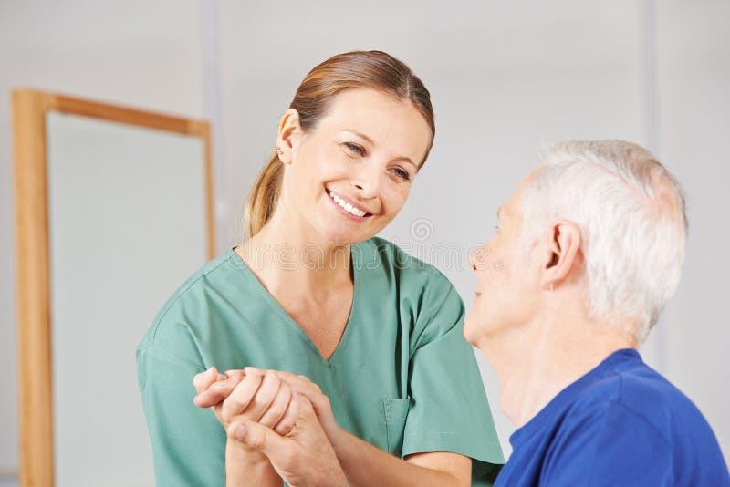 Geriatrisk sjuksköterska med den gamla höga mannen royaltyfria foton