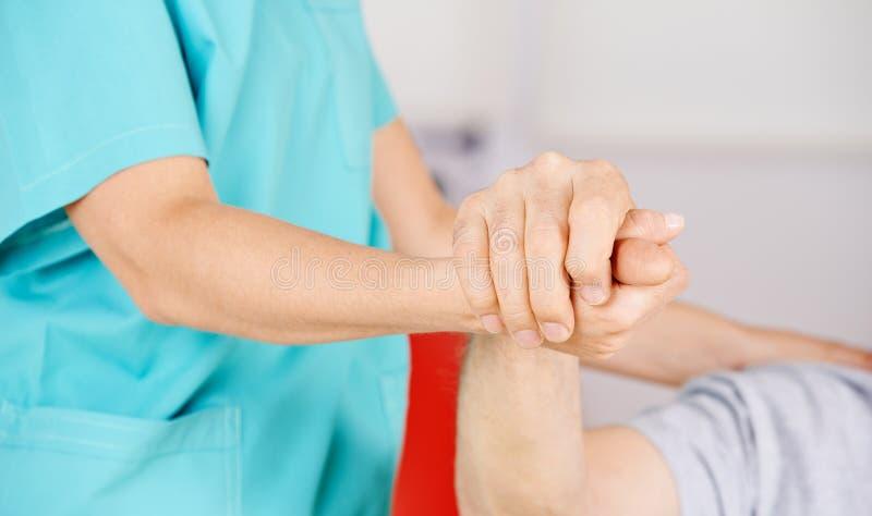 Geriatriska sjuksköterskainnehavhänder av den höga mannen arkivfoton