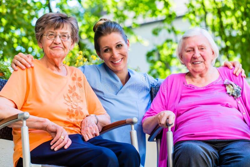 Geriatryczna pielęgniarka ma gadkę z starszymi kobietami obraz royalty free