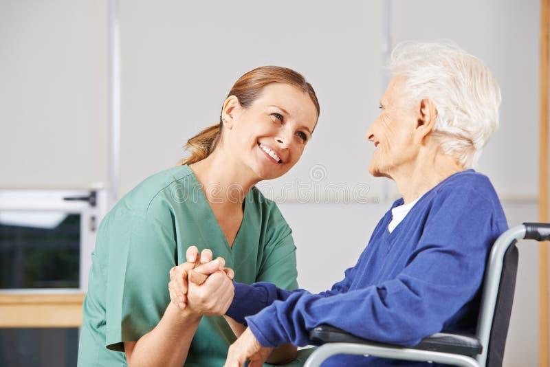 Geriatryczne pielęgniarki mienia ręki z starszą kobietą obraz stock
