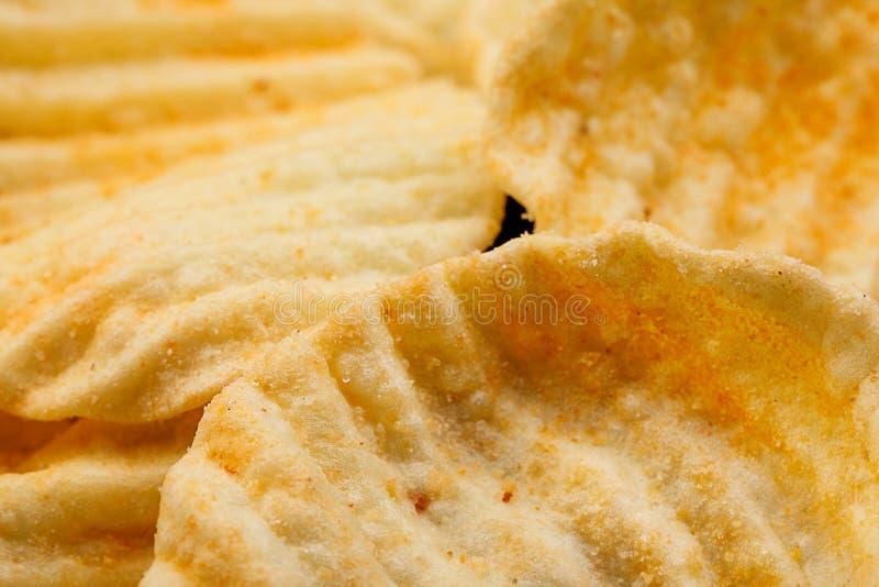 Geribbelde aardappelssnack met peper op zwarte achtergrond Sluit omhoog royalty-vrije stock foto's