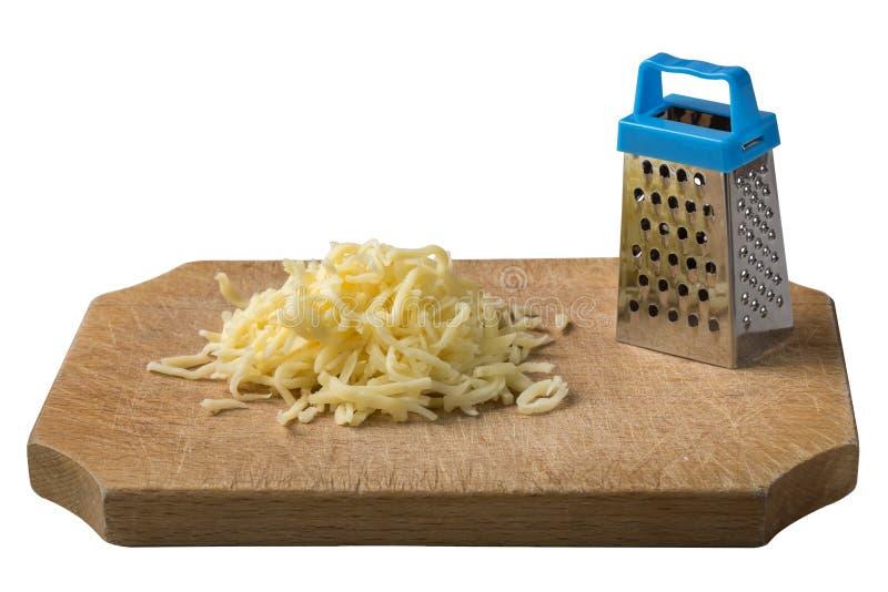 Geriebener Käse auf Holz mit einer wenigen Reibe lokalisiert auf Weiß stockbild