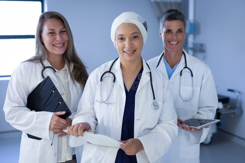 Gerijpte vrouwelijke artsen die zich in het ziekenhuisvloer bevinden stock foto's