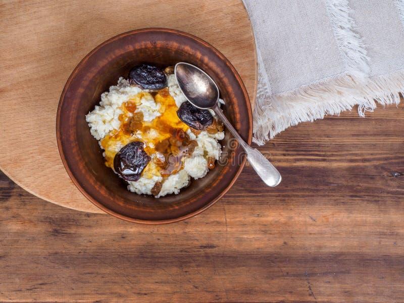 Gerinnen Sie in einer Töpferwarenschüssel mit den Rosinen, und getrocknete Aprikosen nieselten mit Honig auf dem Hintergrund der  stockfoto