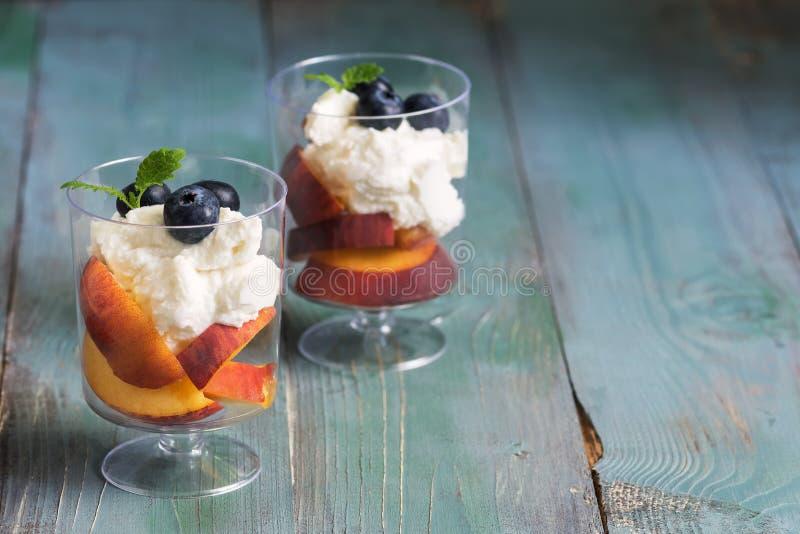 Gerinnen Sie Nachtisch mit Heidelbeere und Pfirsich in einem Glas auf einem grünen rustikalen Holztisch Selektiver Fokus, Kopienr lizenzfreie stockfotografie