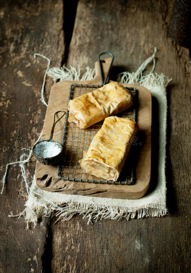 German apfelstrudel or apple strudel. Two freshly baked light flaky German apfelstrudel or apple strudel served on a vintage old rustic wooden board with a royalty free stock image