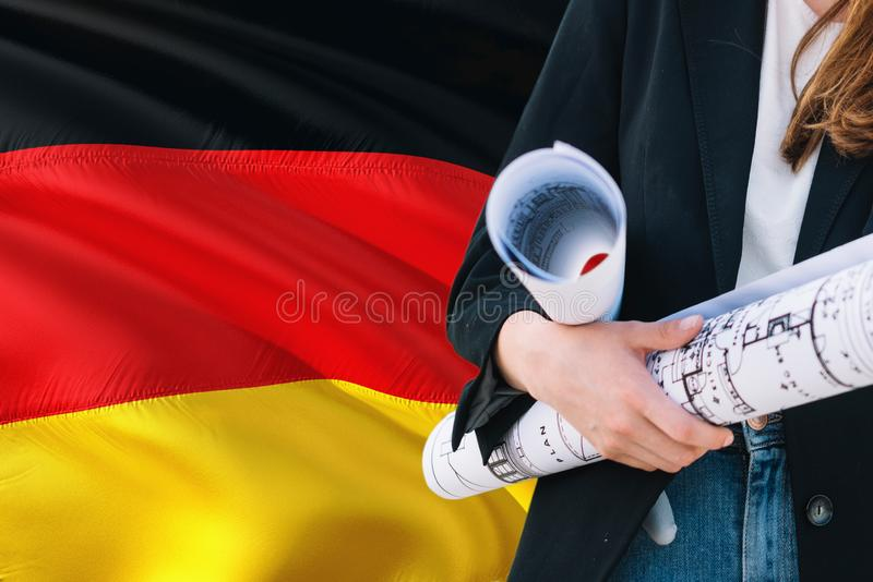German Architect woman holding blueprint against Germany waving flag background. Construction and architecture concept.  royalty free stock images