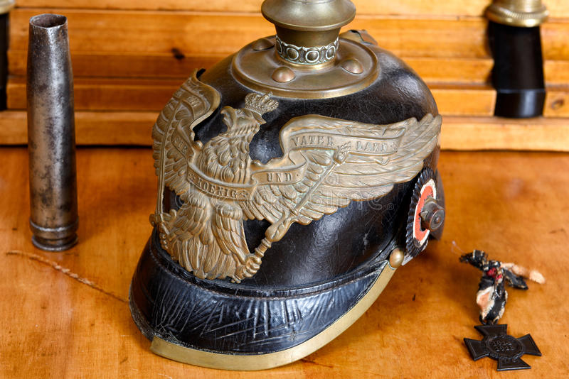 German army helmet (Pickelhaube) from the First World War on an antique cherry wood desk. The inscription on the hemelt is in german language and means: With stock photography