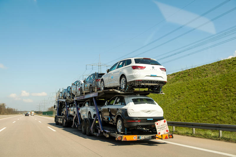 German autobahn with traile transporting cars. GERMANY - MAR 26, 2016: New SEATcars being transported on a trailer on German autobahn on a sunny spring day stock photos