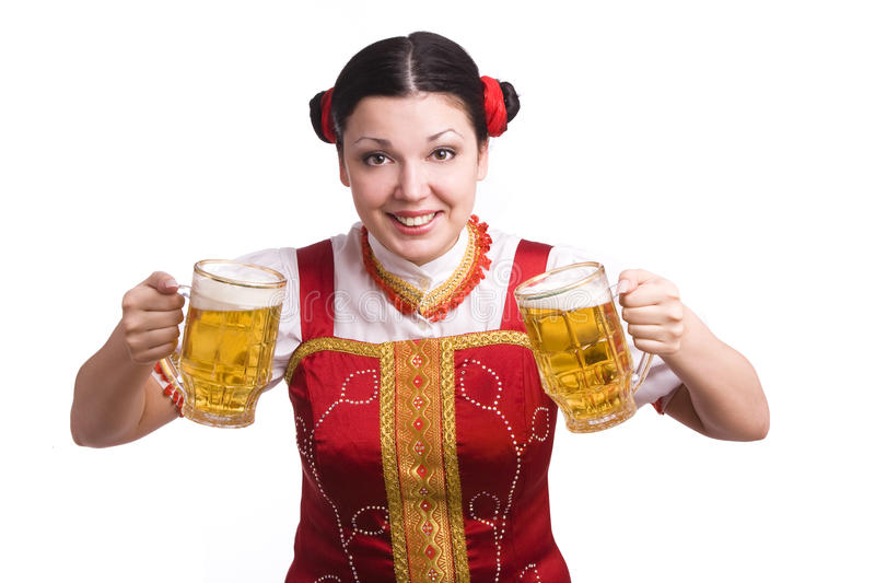 German/Bavarian woman with beer. German/Bavarian girl with a traditional Oktoberfest Ma?krug. Smiling woman in red drindl is holding a beer. Young woman with a stock photo