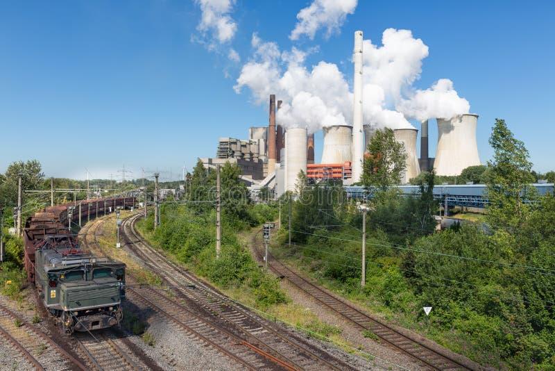 German Coal-fired power plant with empty cargo train near Garzweiler mine. Coal-fired power plant with rempty cargo train near Garzweiler open pit mine in stock photos