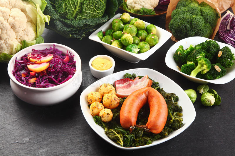 German Cooked Food with Fresh Veggies on Sides. Close up Appetizing German Cooked Food with Sausage, Meat and Potatoes on Boiled Green Leafy Veggies, Placed on stock photos