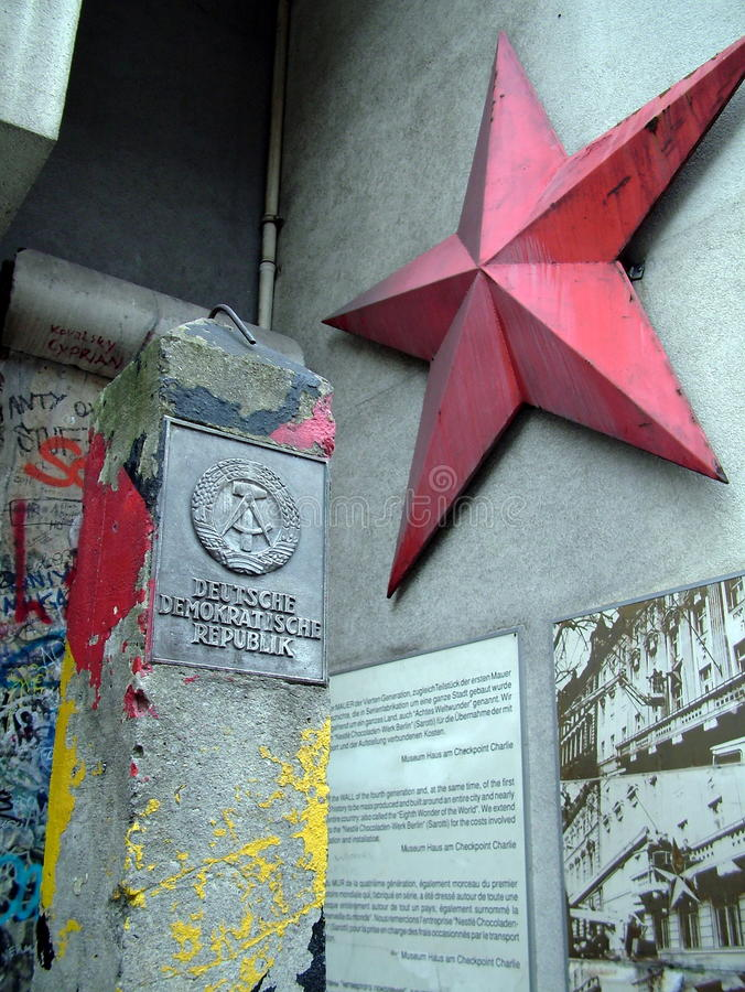 German Democratic Republic sign and red star, Column and Berlin wall portion near Checkpoint Charlie between east and west sectors stock photo