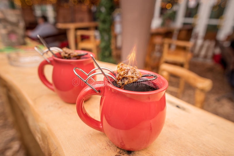 German drink, hot wine and flaming sugar. Image with a mug of hot wine, which has tongs with a flaming cone of sugar on top. It is a traditional german drink at royalty free stock photography