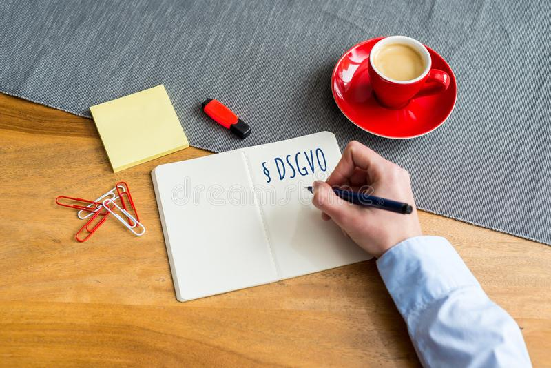 German DSGVO writing on notebook meaning GDPR in english as flat royalty free stock photo