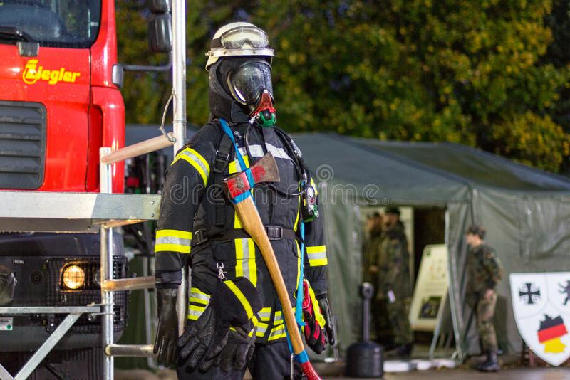 German fireman puppet stands near a fire engine on a presentation royalty free stock photography