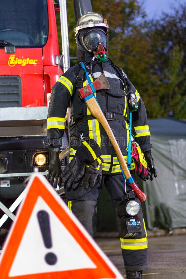 German fireman puppet stands near a fire engine on a presentation stock photography