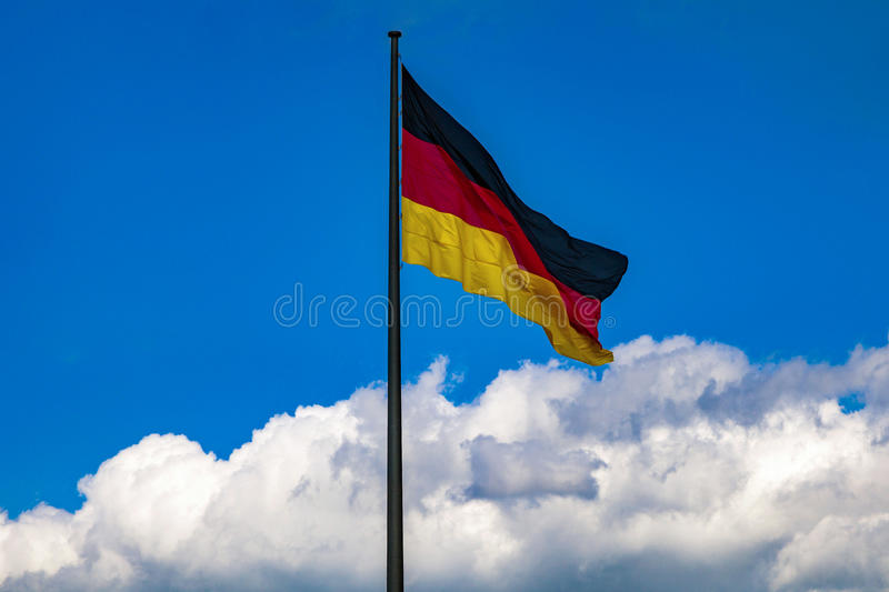 German flag against a bright sky. National flag of Germany against a bright blue sky with clouds stock image