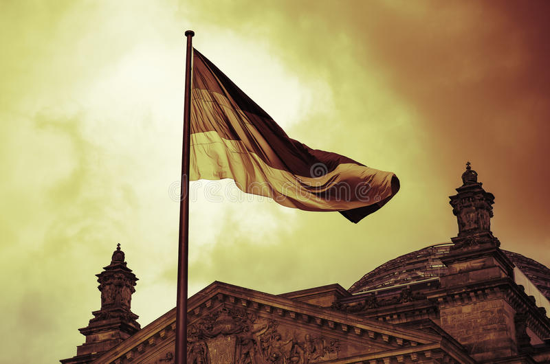 German flag flies above the Reichstag Building in Berlin royalty free stock photography