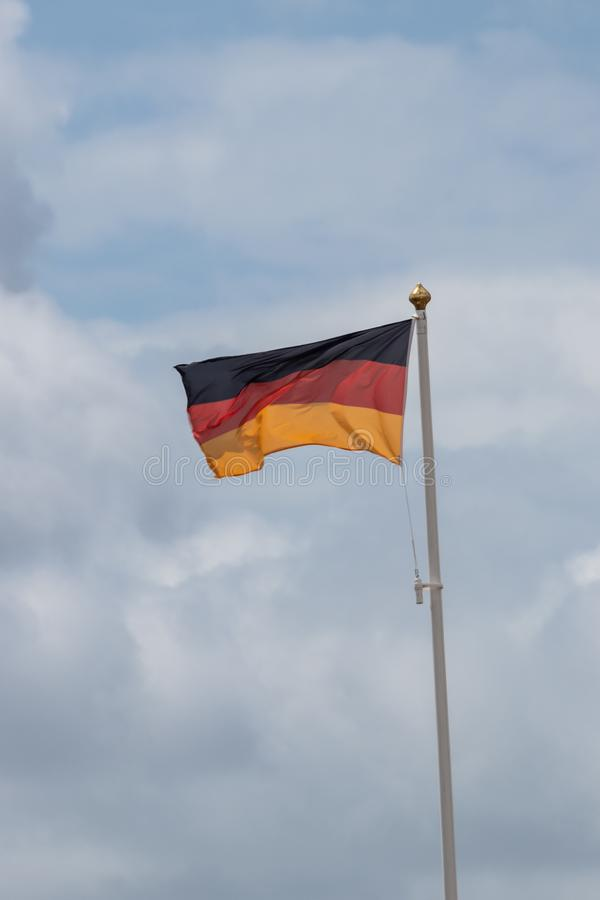 A german flag flying from a flagpole. In the wind royalty free stock photos