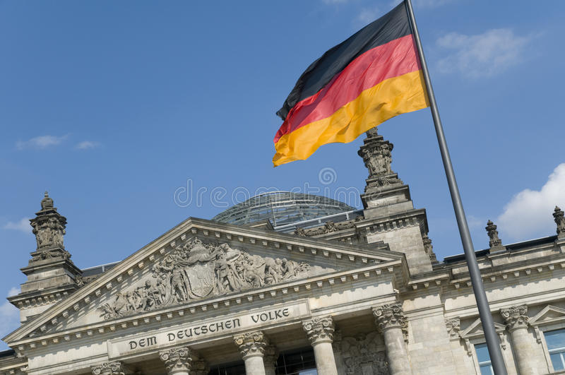 German Flag and Reichstag. The German flag flying in front of the Reichstag in Berlin. The phrase Dem Deutschen Volke (To the German people), designed by Peter royalty free stock photography