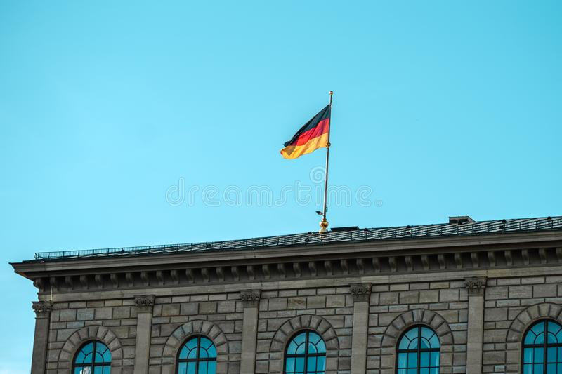 German flag waving on silver flagpole,  building in Munich royalty free stock photo