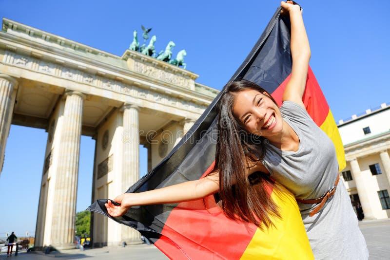 German flag woman happy at Berlin Germany. German flag - Woman happy at Berlin, Germany, Brandenburg Gate cheering celebrating waving flag by Brandenburger Tor royalty free stock images