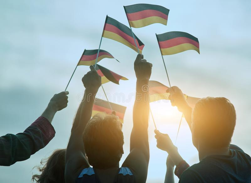 German flags gathering. Raising small deutsch flags to the blue sky, back view royalty free stock image