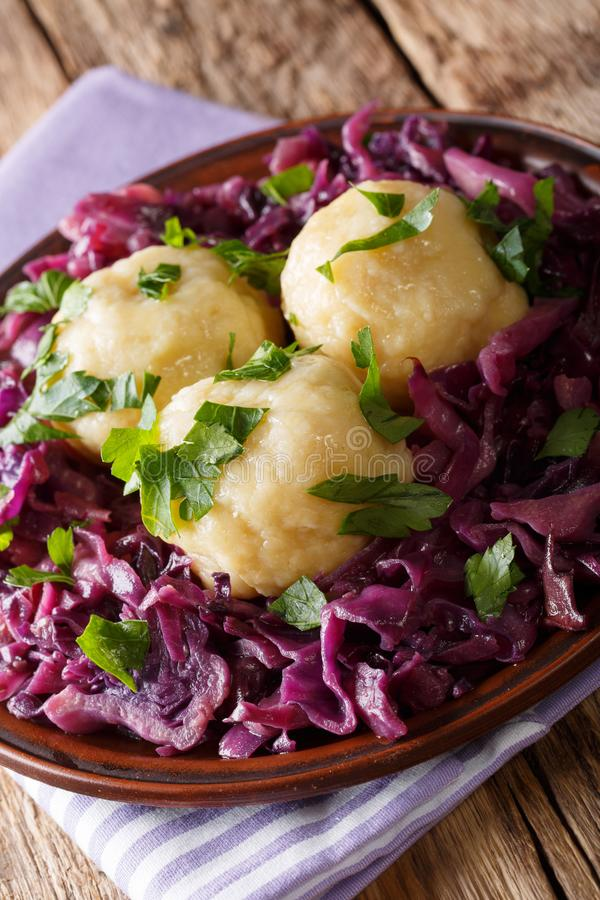 German food knodel potato dumplings and stewed red cabbage close. Up on a plate on the table. vertical royalty free stock photo