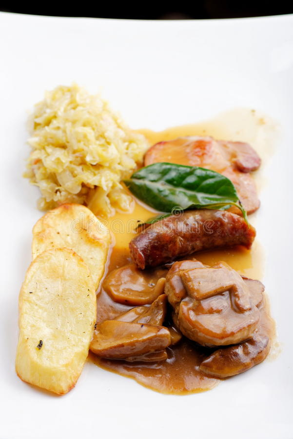 German food, with sausages, steaks, potato and cabbage royalty free stock image