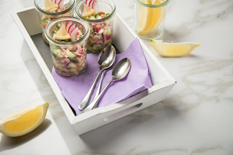 German Friesland north sea brown shrimps salad in glass mug with cucumber, red radish, dill and lemon on wooden tray and marble. Table stock photos