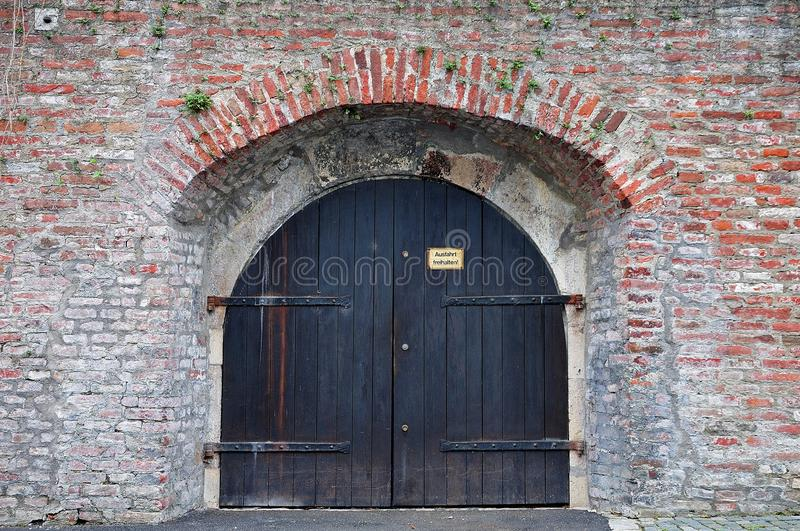 German inscription `keep exit free` at old wooden gate. Old wooden gate in a city wall of bricks with inscription in german language: `keep exit free stock image