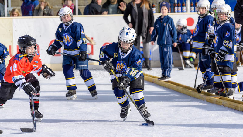 German kids playing ice hockey. Fuerstenfeldbruck, Bavaria, Germany - 06. February 2016: German Kids playing ice hockey. Age is about 10 years. Orange Player on stock photo
