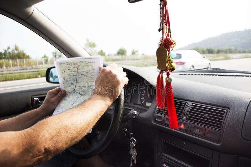 German old man driving car and looking map go to Sandhausen. District pass at Speyer town in Rhineland-Palatinate, Germany royalty free stock images