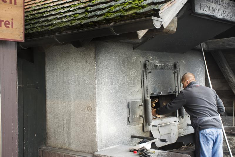 German old men use firewood stove old style cooking bread at restaurant. Near Mummelsee lake in Black Forest or Schwarzwald on September 9, 2017 in Stuttgart stock photo