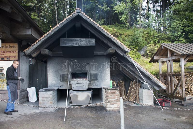German old men use firewood stove old style cooking bread at restaurant. Near Mummelsee lake in Black Forest or Schwarzwald on September 9, 2017 in Stuttgart royalty free stock image