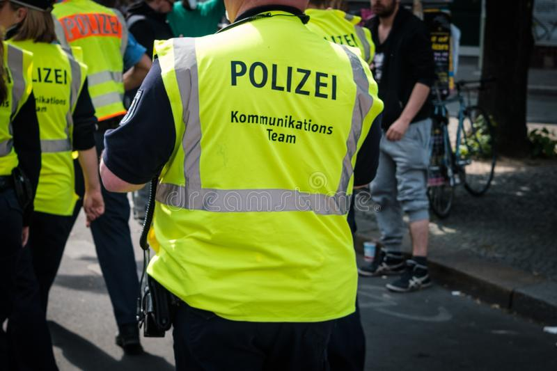 German police from behind in crowded street parade on labor day in Berlin. Berlin, Germany - May 01, 2019: German police from behind in crowded street parade on stock image